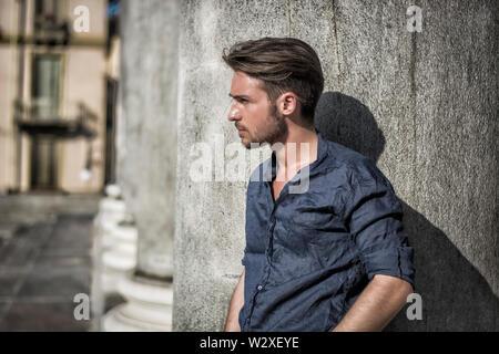 Un beau jeune homme en milieu urbain en journée d'été, wearing blue shirt, appuyé contre la colonne ou pilier de pierre Banque D'Images