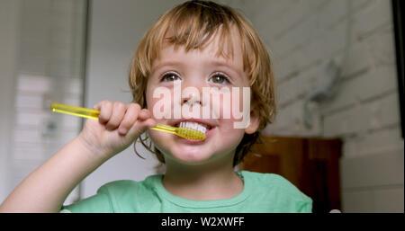 Petit garçon blond se brosser les dents d'apprentissage Banque D'Images