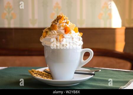 Café avec crème fouettée et les fruits secs en tchèque blanc sur une table dans un café avec un petit biscuit sur une soucoupe, cuillère et la paille. Délicieux dessert en t Banque D'Images
