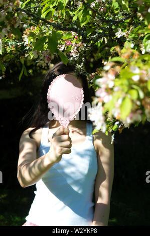 Un auto-portrait avec un arbre en fleurs et un miroir rose cachant mon visage. Banque D'Images