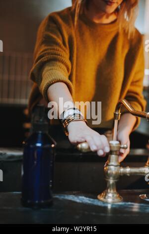 Une femelle dans un pull-over chaud avec sa main sur la manivelle à laver ses mains Banque D'Images