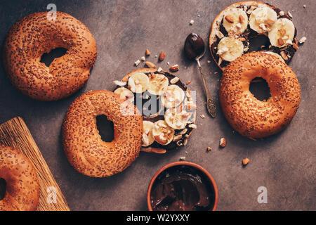 Des bagels aux graines de sésame, crème au chocolat, banane et noix sur une base rustique. Mise à plat,les frais généraux. Banque D'Images
