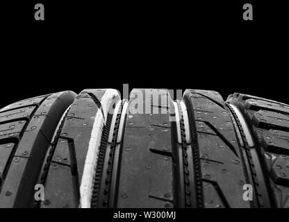 Portrait d'un ensemble de pneus d'été sur fond noir. Pile de pneus arrière-plan. Pneu de voiture protector close up. Pneu en caoutchouc noir. Tout nouveau tir voiture