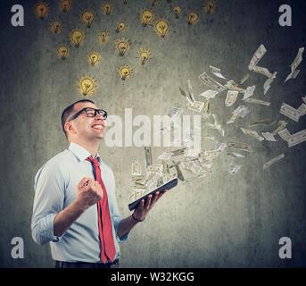 Businessman avec des idées brillantes et tablette à créer de bonnes affaires en ligne gagner de l'argent comptant des dollars tomber vers le bas.