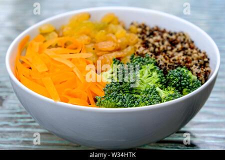 Bol de quinoa aux légumes et Golden sultanines séché, brocoli et carottes râpées Banque D'Images