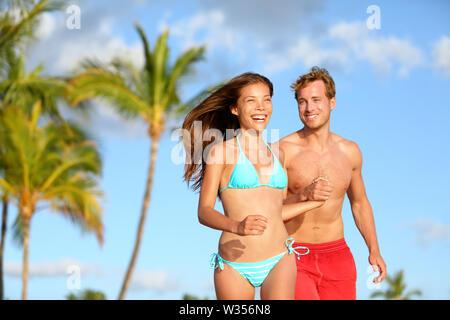 Couple on beach vacation travel laughing bonne course ensemble ludique et joyeux. Woman in bikini et l'homme en maillot de bain. Les amateurs de beaux minets amoureux en lune de miel sur Hawaii. Banque D'Images