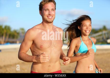 L'exécution de athletic couple jogging sur la plage de la formation dans les vêtements de plage maillot de bain, maillot et short. Bel homme torse nu modèle de remise en forme et belle mixed race woman asiatiques heureux et souriants. Banque D'Images