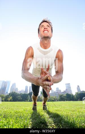 Clap pousées homme fitness dans Central Park à New York. Mettre en place la formation des athlètes masculins push-ups à l'extérieur sur l'herbe sur Manhattan, New York City, USA. Banque D'Images