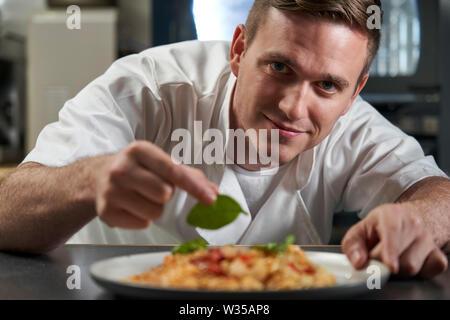 Portrait Of Male Chef Garniture assiette de nourriture dans la cuisine professionnelle Banque D'Images