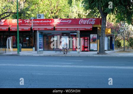 Un homme âgé attend que le bus tôt un dimanche matin tranquille en dehors de la Hermanos Gómez Jardines de Murillo restaurant bar à Sevilla, Espagne. Banque D'Images