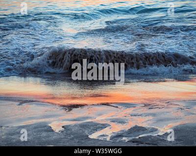 Close up d'une vague se brisant sur une plage de sable fin avec reflet dans l'eau Banque D'Images