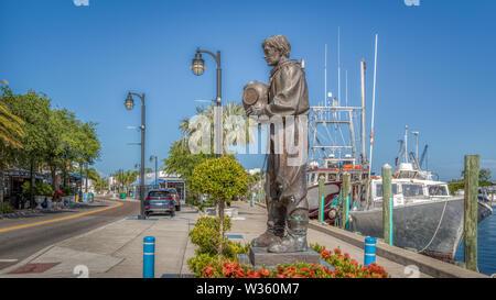 Tarpon Springs, en Floride. Une petite ville au bord de l'historique avec une éponge diver statue sur les quais à côté de bateaux. Banque D'Images