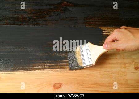 Main tenant le pinceau peinture la surface de meubles en bois avec de la peinture gris foncé Banque D'Images
