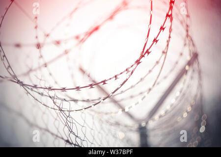 Clôture en treillis métallique, qui est enroulé sur le haut d'une spirale de fil de fer barbelé, a mis en lumière rouge. L'image est au sujet de la criminalité, et la couleur rouge signifie danger un