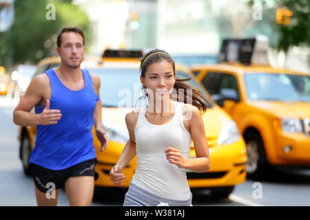 Couple actif fonctionnant sur la célèbre rue commerçante de la cinquième avenue à Manhattan, New York City New York, USA. Exercise Lifestyle portrait of young asian woman runner et caucasien homme jogger.