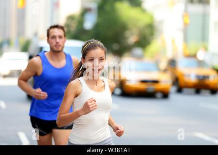 Ville porteur - urbain new-yorkais des gens courir dans la rue animée de New York NEW YORK. Les jeunes adultes caucasiens asiatiques jogging en trafic sur Manhattan en été.