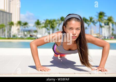 Push-ups woman doing pushups fitness toning arms à l'extérieur sur beachwalk. Mettre en place le sport féminin fille modèle crossfit formation l'exercice à l'extérieur. Young Asian Woman sport sportif dans son 20s. Banque D'Images