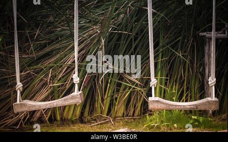 Jeux pour enfants sur swing vide, les enfants dans le parc, balançoire en bois, sol en bois Banque D'Images