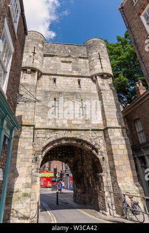 Bar Bootham, York. Une ancienne porte de la ville debout à la fin d'une rue. Les magasins sont de chaque côté et un scolairecoût est visible à travers l'arche. Banque D'Images
