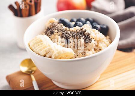 Gruau d'avoine avec des bleuets, bananes et chia seeds dans un bol. Vue rapprochée, selective focus, tonique de l'image. Petit déjeuner santé alimentation. Concept de nettoyage Banque D'Images