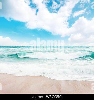 Les vagues de la mer qui s'écrase sur une plage de sable fin. superbe temps ensoleillé avec des nuages sur l'horizon. des eaux émeraude sous un ciel d'azur. beauté et la puissance de la nature con