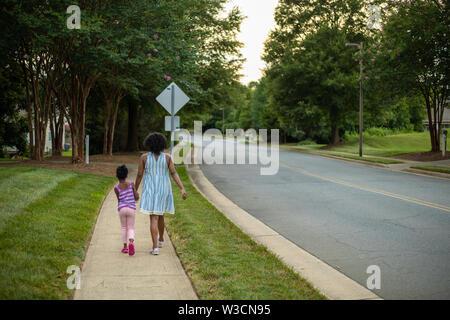 Une mère noire et sa fille marcher sur un trottoir holding hands Banque D'Images