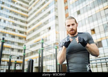 Certain beau jeune homme avec barbe rouge portant des gants de boxe pratiquer seul sur un terrain de sport Banque D'Images