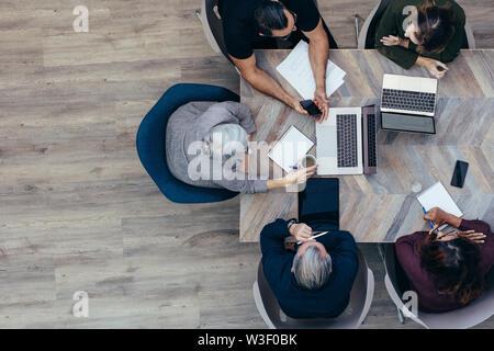 Vue de dessus od senior businesswoman discuter avec ses collègues. Réunion de l'équipe d'affaires dans le bureau.