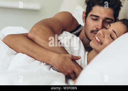 Beautiful happy young couple hugging tout en dormant sur le lit. Young man and woman lying together in bed.