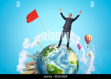 Petite Planète Terre avec la ville moderne d'apparaître d'un côté et les ballons à air chaud flying in sky, et heureux d'affaires qui a planté le drapeau rouge Banque D'Images