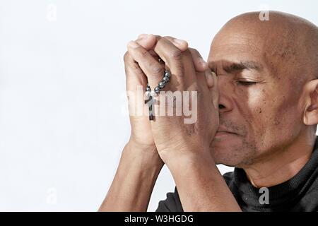 Homme noir à prier Dieu avec croix et les mains ensemble Caraïbes homme priant avec fond blanc stock image stock photo
