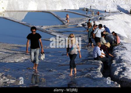Les touristes à pied à travers les piscines thermales à la travertins (château de coton) à Pamukkale en Turquie. Banque D'Images