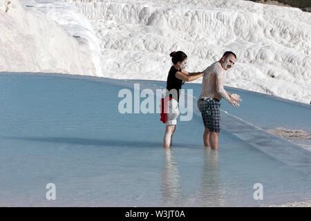 Les baigneurs profiter frottant la boue riche en minéraux les uns sur les autres organes dans l'une des piscines thermales à la travertins (château de coton) à Pamukkale, Turquie. Banque D'Images