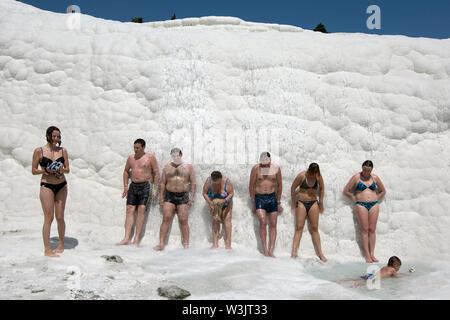 Les baigneurs se détendre contre une falaise comme l'eau thermale coule sur eux à la travertins (château de coton) à Pamukkale en Turquie. Banque D'Images