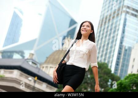 Asian Business woman walking en dehors de Hong Kong. Asian businesswoman office worker dans quartier des affaires du centre-ville. Jeune asiatique chinois multiraciale / Caucasian female professional dans le centre de Hong Kong Banque D'Images