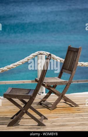 Des chaises en bois sur une plate-forme de pont à Agios Nikolaos plage sur l'île de Zakynthos, Grèce Banque D'Images