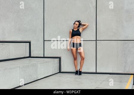 Femme se reposant après l'entraînement. Toute la longueur de sporty young woman relaxing après exécution de l'exercice.