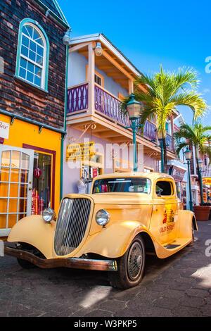 Sint Maarten / Caraïbes / Pays-Bas - Janvier 23,2008: vue sur le jaune vintage voiture garée dans la rue avec des bâtiments colorés et de palmiers. Banque D'Images