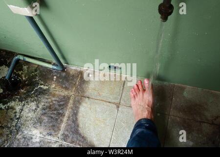 Blurred motion de l'écoulement de l'eau sur les orteils du pied gauche d'un homme asiatique Banque D'Images