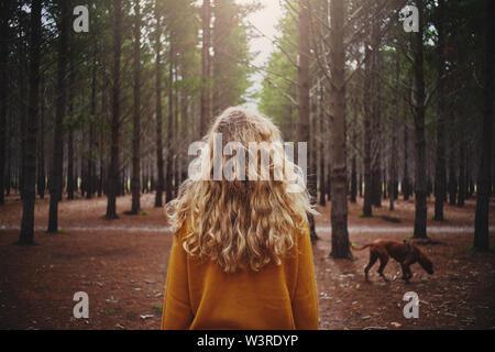Jeune femme blonde avec son chien dans la forêt
