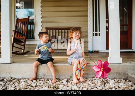 Jeune garçon et fille assise sur le porche avant de manger les sucettes glacées Banque D'Images