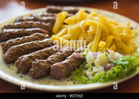 Cevapi, spécialité traditionnelle serbe avec frites, salade verte et l'oignon Banque D'Images
