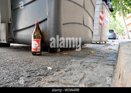 Une bouteille d'un litre de bière traditionnelle Alhmabra abandonné le long de la rue près d'une corbeille et des trottoirs à Grenade, Espagne. Banque D'Images
