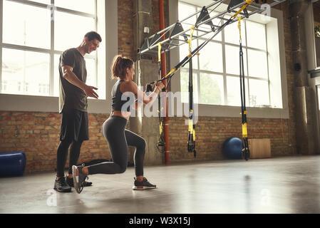 Quel entraînement. Belle jeune femme en faisant des exercices de sport trx à gym alors que son entraîneur personnel est debout à côté d'elle. Formation TRX. L'exercice ensemble. Mode de vie actif