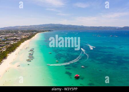Seascape Aux Philippines par temps ensoleillé, vue de dessus. Mer transparente et bateaux de touristes près de l'île de Boracay. Immeubles résidentiels et hôtels sur la grande île.