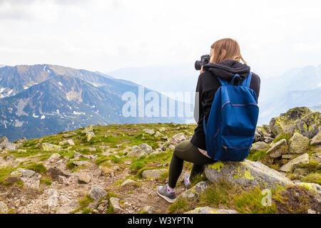 Jeune blonde voyages avec un sac à dos bleu, se trouve au sommet d'une montagne et prend des photos du paysage de montagne verte. Vue arrière Banque D'Images