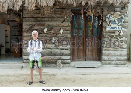 Un homme debout en face d'une boutique de l'art et l'artisanat local dans la région de Isla Holbox, Mexique Banque D'Images