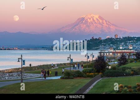 Mt Rainier plane sur le centre-ville de Tacoma et baie de lancement comme vu du point Ruston avec personnes à pied et une mouette Banque D'Images