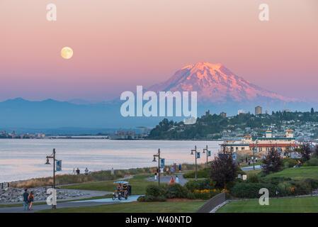 Mt Rainier plane sur le centre-ville de Tacoma et baie de lancement comme vu du point Ruston avec personnes à pied et faire du vélo Banque D'Images