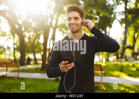 Portrait of handsome athletic homme vêtu de vêtements de sport à l'écoute de la musique avec vos écouteurs et smartphone tout en faisant de l'exercice dans sunny green park Banque D'Images